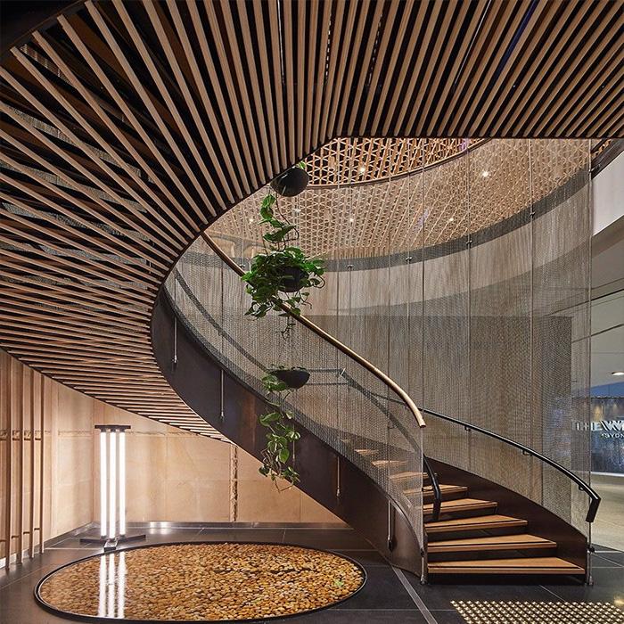 винтовая лестница с ограждением из стекла и декоративной отделкой